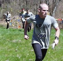 young man in ARMY t-shirt running up a hill, with three others trailing
